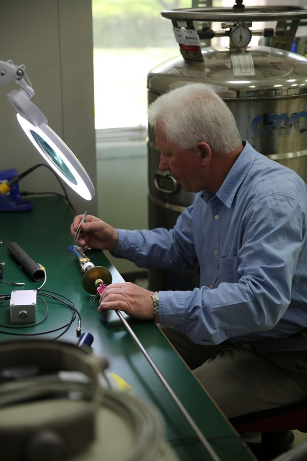 Dr. Matlashov is installing a microstrip SQUID amplifier sample on a cryogenic probe for testing it at 4.2 K inside a liquid Helium transport dewar.